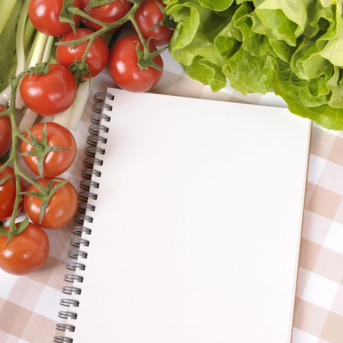 Selection of salad vegetables with blank recipe book or shopping list on a check tablecloth.